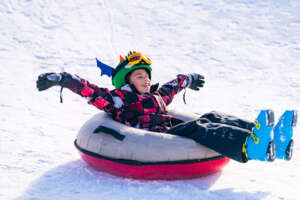 Child in Snow Tube Sledding Downhill