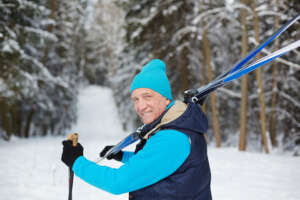 Happy aged sportsman carrying skiing equipment while moving to forest on winter day